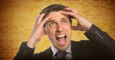 is troubled: Digital composite of Business man hands on head against yellow brick wall Stock Photo