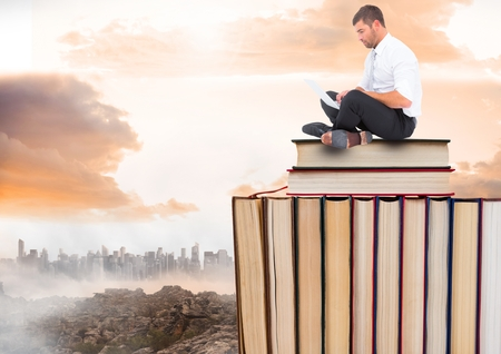 Digital composite of Man with laptop sitting on Books stacked by distant city and clouds