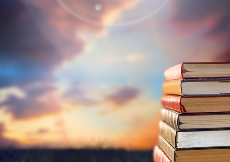 Digital composite of Woman sitting on Books stacked by sunset sky Stock Photo