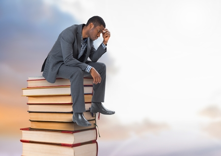 Digital composite of Businessman sitting onBooks stacked by cloudy sky