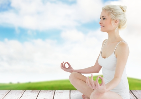 tied in: Digital composite of Woman Meditating by green field