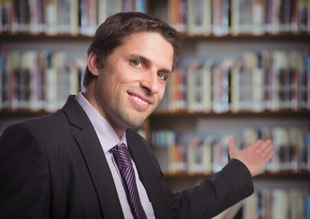 Digital composite of Business man gesturing towards blurry bookshelf