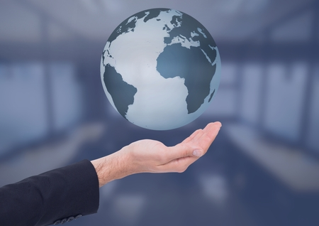 Digital composite of Open palm business hand holding world earth globe in front of blue room