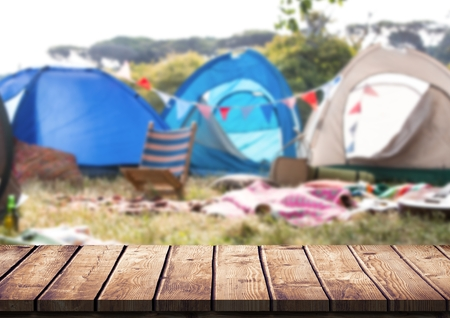 Digital composite of Wood table against blurry campsite
