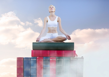 Digital composite of Woman meditating relaxing on Books stacked by sky