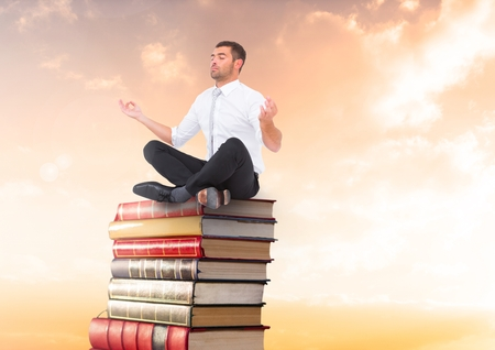 Digital composite of Businessman meditating sitting on Books stacked by sunset with laptop Stock Photo