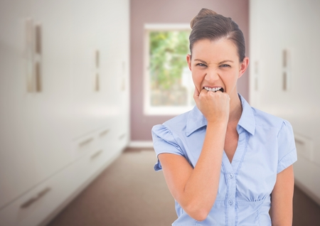 Digital composite of Stressed woman biting hand in room Stock Photo