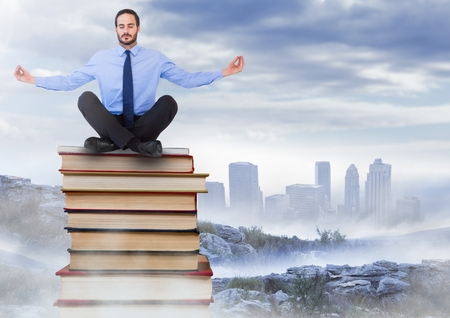Digital composite of Businessman sitting meditating on Books stacked by distant city Stock Photo