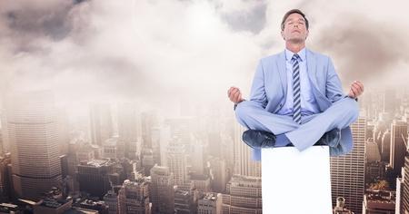 Digital composite of Businessman Meditating on plinth over city