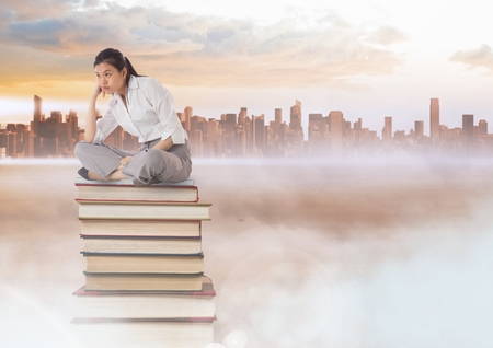 Digital composite of Businesswoman sitting on Books stacked by distant city
