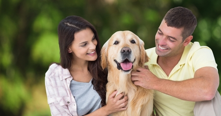 Digital composite of Couple with dog against blurry green background