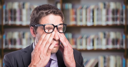 tensed: Digital composite of Business man rubbing eyes against blurry bookshelf