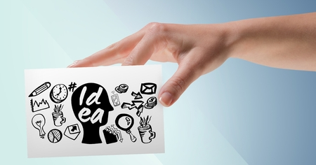 Digital composite of Hand with card and black idea doodles against blue background Stock Photo