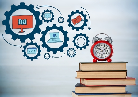 Digital composite of Pile of books and clock with blue gear graphics against blurry grey wood panel Stock Photo