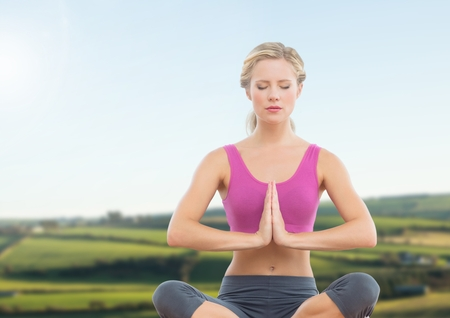 Digital composite of Woman Meditating by green fields Stock Photo