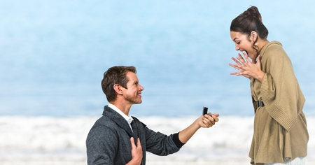 Digital composite of Man propsing to woman against blurry beach