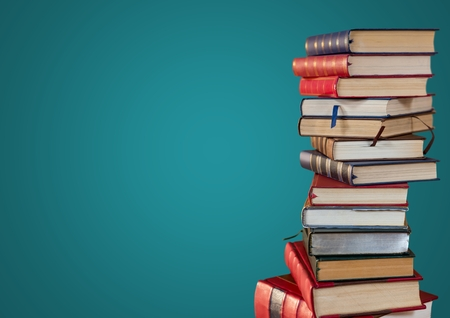 Digital composite of Pile of books against teal background Stock Photo
