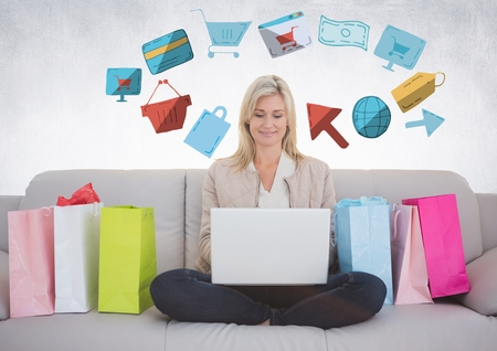 spending: Digital composite of Woman on couch with shopping bags and online shopping graphic drawings Stock Photo