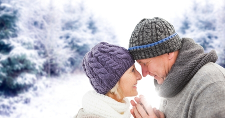 Digital composite of Elderly couple in snowy landscape with flare Stock Photo