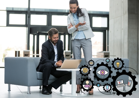 woman cellphone: Digital composite of Business man and woman looking at laptop with black gear graphics Stock Photo