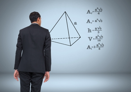Digital composite of Businessman looking at equations graphic drawings Stock Photo