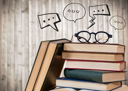 Digital composite of Pile of books and glasses with black speech bubbles against blurry wood panel Stock Photo