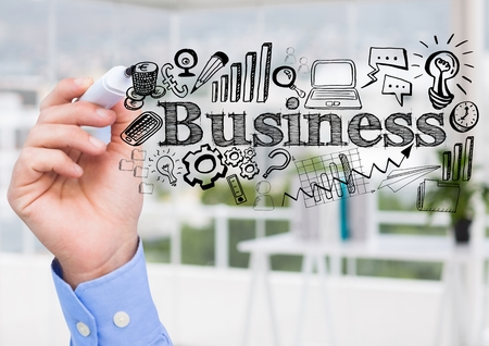Digital composite of Hand with pen and black business doodles against blurry office Stock Photo