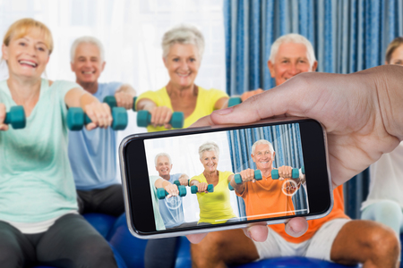 nursing class: Hand holding mobile phone against white background against portrait of seniors using exercise ball and weights