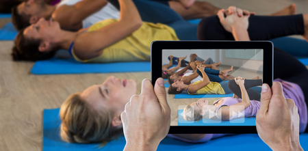 Cropped hand holding digital tablet against group of people doing leg flexes