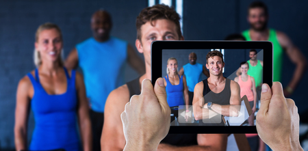 Composite image of cropped hand holding digital tablet