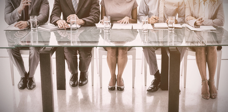 Panel of corporate personnel officers sitting at table in office Stock Photo
