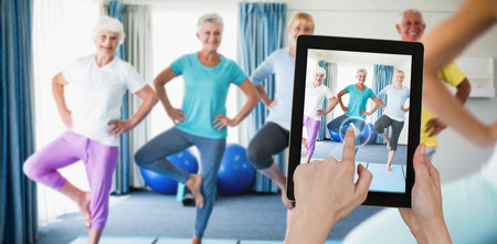 Hands touching digital tablet against white background against instructor performing yoga with seniors