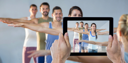 Computer instruction: Cropped hand holding digital tablet against instructor taking yoga class Stock Photo