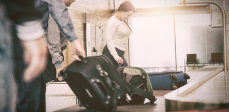 People carrying luggage from baggage claim at airport Stock Photo