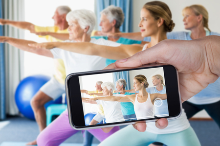 Hand holding mobile phone against white background against instructor performing yoga with seniors