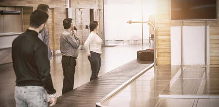 adult  body writing: People waiting by baggage claim for luggage at airport Stock Photo