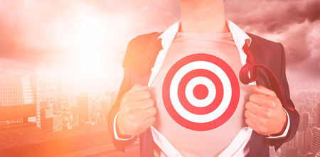 Businessman opening shirt with sports target while standing against cityscape