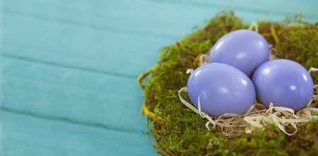 Close-up of violet Easter eggs against blue wood background Stock Photo
