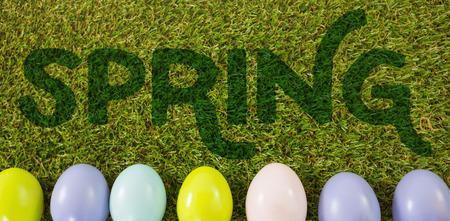 Pasen-groet tegen gekleurde paaseieren op gras