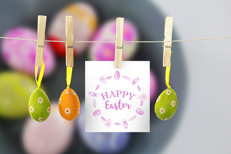 Happy easter logo against bowl with painted easter eggs on white background