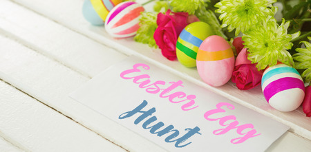 Easter greeting against painted easter eggs with flowers
