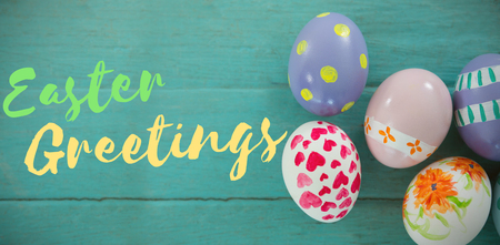 cropped: Easter greeting against painted easter eggs on wooden surface Stock Photo