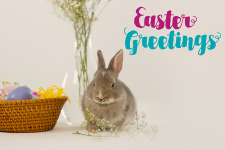 wicker work: Easter greeting against basket with easter eggs and easter bunny