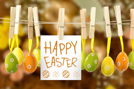 Easter greeting against golden easter eggs with flowers in nest Stock Photo