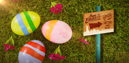 Easter egg hunt sign against painted easter egg on grass Stock Photo