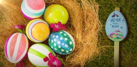 Easter egg hunt sign against painted easter eggs in nest Stock Photo