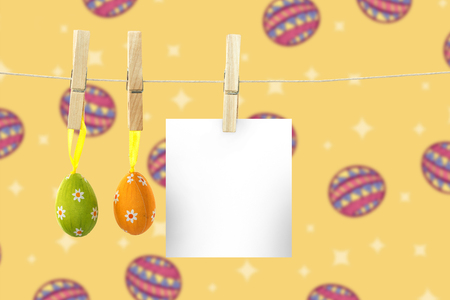 hanging easter eggs against easter eggs on yellow background