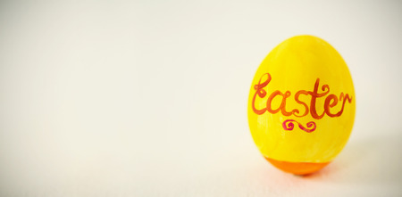 up code: Close-up of Easter text written on egg against white background Stock Photo