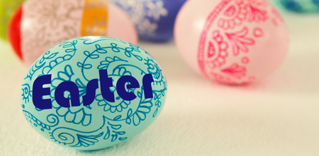 Easter greeting against colorful easter eggs on white background Stock Photo