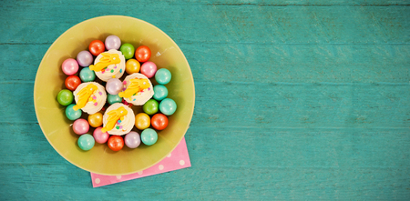 up code: Colorful chocolates and cupcakes in bowl on wooden surface Stock Photo